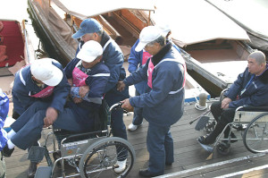 Picture of a wheelchair being carried to the boat at a barrier-free transportation lecture